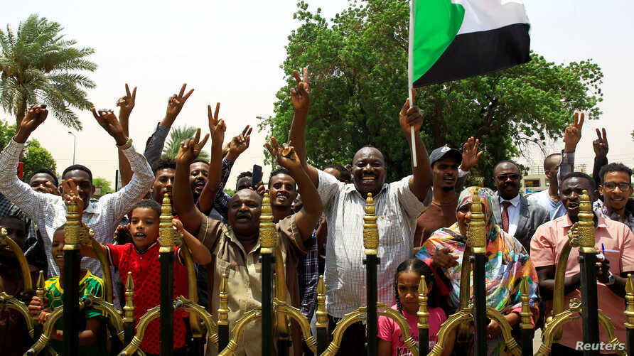 FILE - Sudanese people celebrate the signing of a constitutional declaration between the deputy head of the Sudanese Transitional Military Council, Mohamed Hamdan Dagalo, and Sudan's opposition alliance leader Ahmad al-Rabiah, in Khartoum, Aug. 4, 2019.