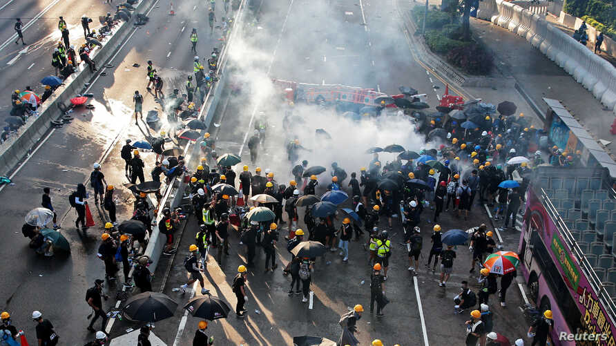 Demonstrators disperse after a tear gas is fired by Hong Kong police in Hardcourt Road, Admiralty, in Hong Kong, China, Aug. 5, 2019.