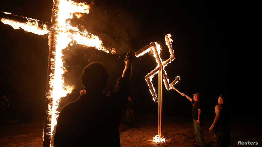 FILE - Members of a white nationalist group burn a swastika and cross outside Atkins, Arkansas, March 9, 2019. The publisher of a neo-Nazi website has been ordered to pay a Jewish woman$14 million for inciting his readers to harass her family.