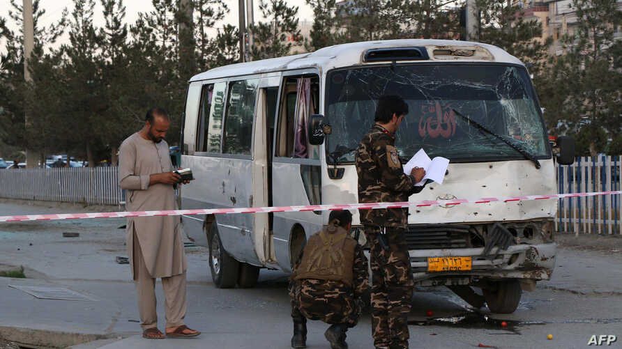 Afghan security personnel investigate a damage bus carrying employees of Khurshid TV, at the site of a bomb blast in Kabul, August 4, 2019.