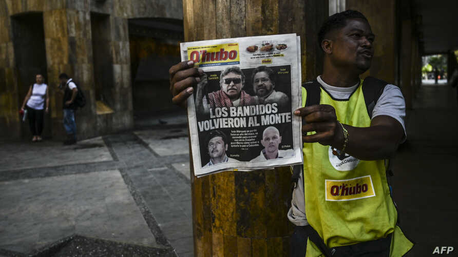 A vendor sells a newspaper in Medellin, Aug. 30, 2019, fronted with pictures of former senior commander of the dissolved FARC rebel army group in Colombia, Ivan Marquez, a day after he announced he was taking up arms again along with other guerrillas.
