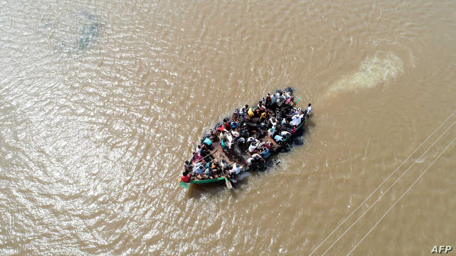 An aerial view of locals being rescued on a boat in waterlogged Jamkhandi Taluk at Belgaum district of Karnataka state in the south Indian city of Bangalore, Aug. 11, 2019.