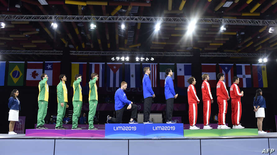 American fencer Race Imboden (4th from L) kneels during the national anthem at the Men's Foil Team medal ceremony in Fencing, at the Lima Convention Center during the Pan American Games Lima 2019, in Lima, Peru, Aug. 09, 2019.