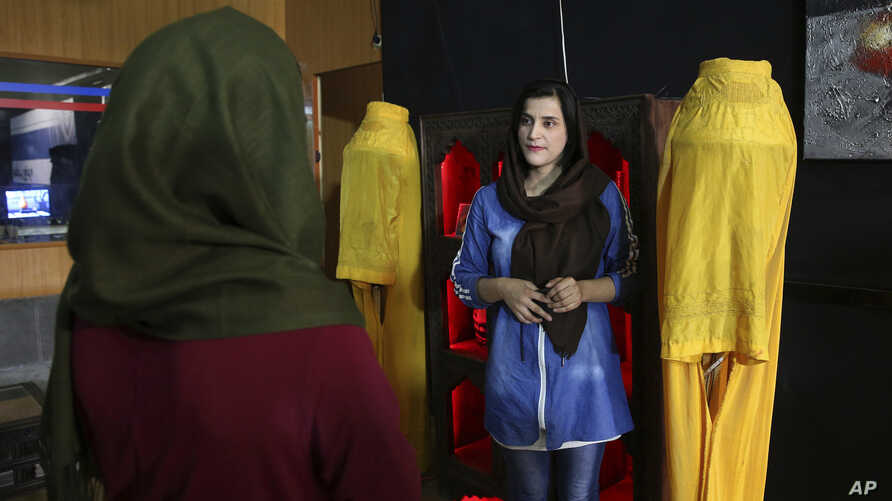 Shogofa Sadiqi, right, chief director of Zan TV speaks with a staff member among a display of burqas at her office in Kabul, Afghanistan, Aug. 24, 2019.