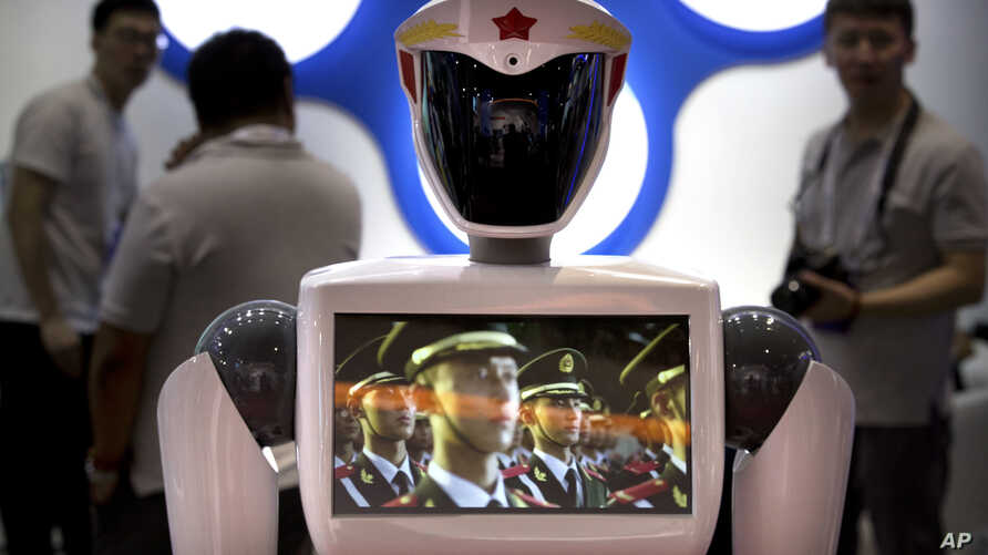A video screen plays footage of Chinese People's Liberation Army (PLA) soldiers on a robot from a Chinese robot maker at the World Robot Conference in Beijing, China, Aug. 15, 2018.