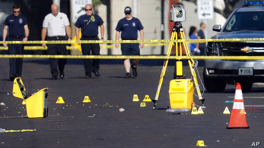 Evidence markers rest on the street at the scene of a mass shooting, Aug. 4, 2019, in Dayton, Ohio.