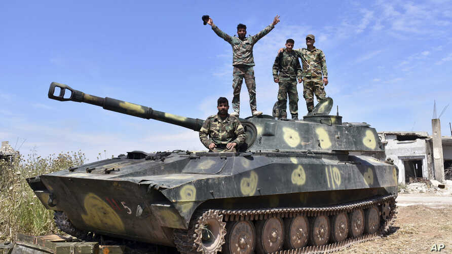 In this photo released by the Syrian official news agency SANA, Syrian army soldiers flash the victory sign as they stand on their tank in the village of Kfar Nabuda, in the countryside of Hama province, Syria, May 11, 2019.