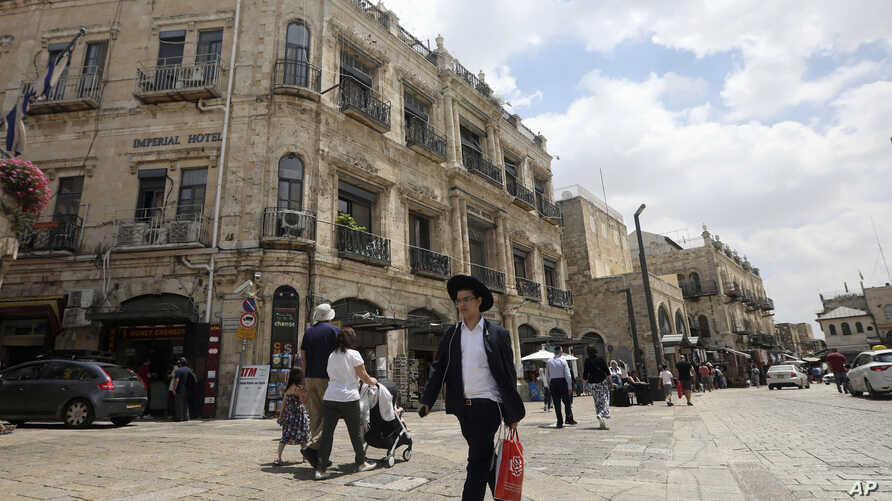 People walk past the Palestinian-run Imperial Hotel that is part of a legal battle, in Jerusalem's Old City, June 13, 2019.