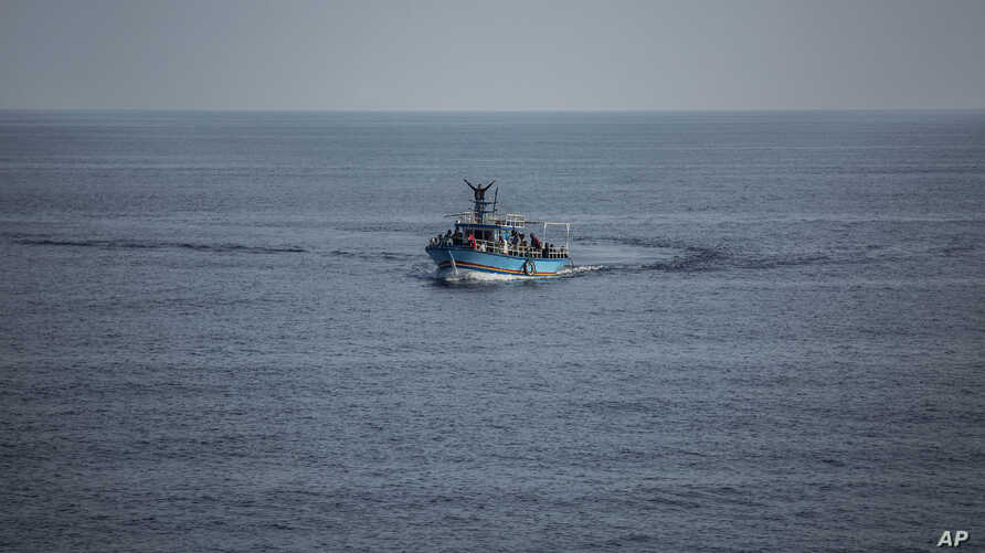 A migrant waves from a boat June 30, 2019, later escorted to the Italian island of Lampedusa.