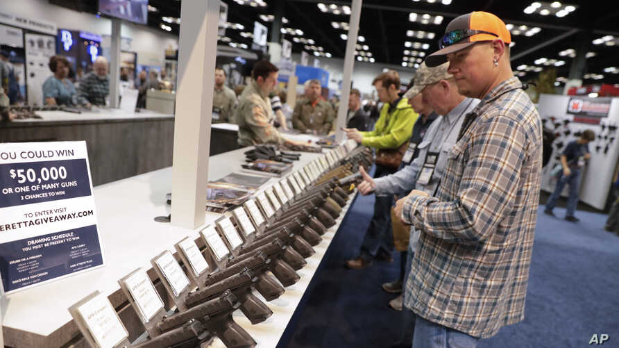 A gun enthusiast looks over a display of pistols in the exhibition hall at the National Rifle Association Annual Meeting in Indianapolis, April 27, 2019.