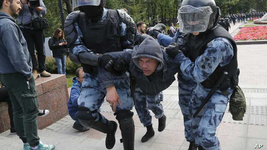 Police officers detain a protester during a rally in the center of Moscow, Russia, Aug. 3, 2019.