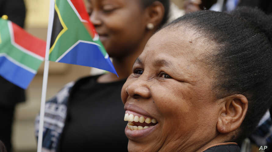 People hold South African flags as Nelson Mandela Foundation CEO, Sello Hatang speaks to the press on the steps of the Johannesburg High Court, Aug. 21, 2019, after South Africa's Equality Court restricted the display of the old apartheid-era flag.