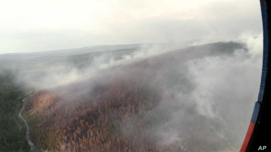 FILE - This image made from video provided by RU-RTR Russian television channel shows a view of a forest fire in the Boguchansky district of the Krasnoyarsk region, Russia Far East, July 31, 2019.
