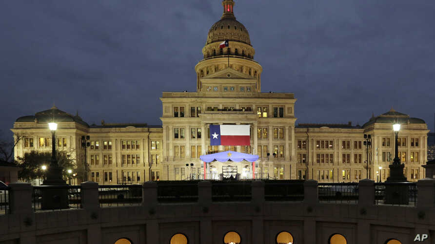 A large Texas flag hangs from the Texas State Capitol in Austin, Texas, Jan. 14, 2019.