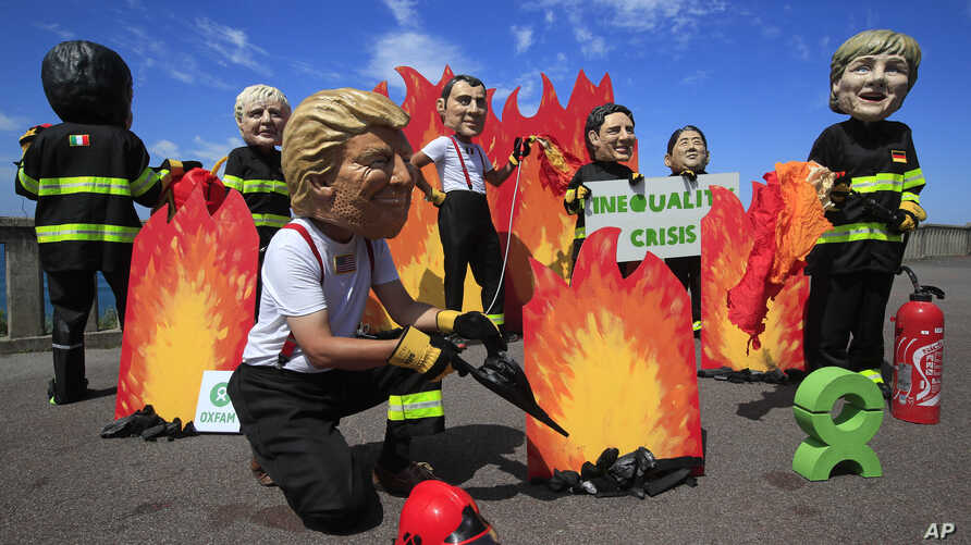 A man wearing a Trump mask, center, is joined by other 'world leaders' during a protest ahead of the G-7 summit in Biarritz, France, Aug. 23, 2019.