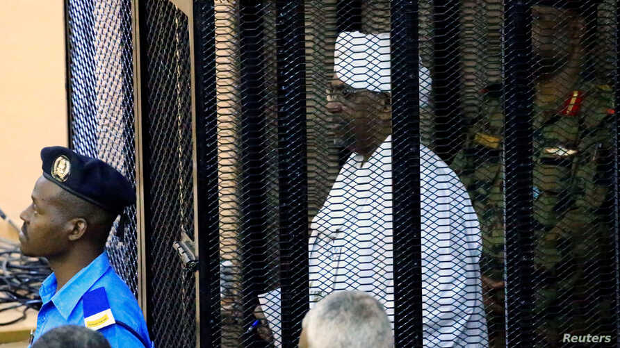 Sudan's former president Omar Hassan al-Bashir stands guarded inside a cage at the courthouse where he is facing corruption charges, in Khartoum, Sudan, Aug. 19, 2019.