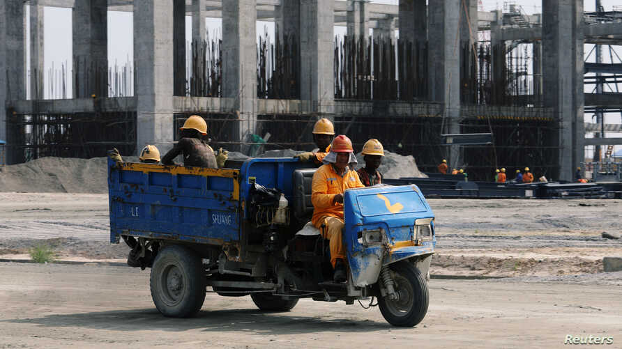 Workers ride in a vehicle at the construction site of the Dangote oil refinery in Ibeju Lekki district, on the outskirts of Lagos, Nigeria, Aug. 7, 2019.