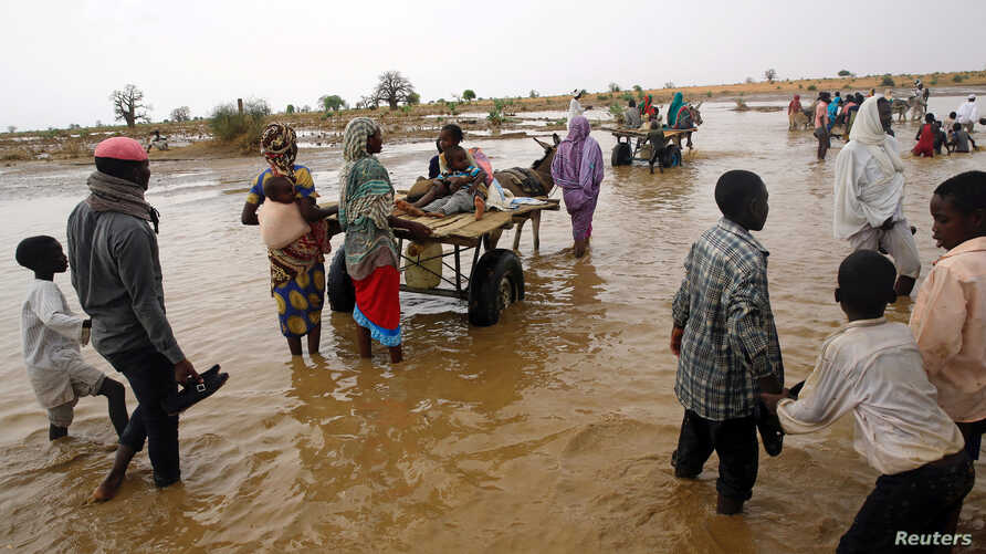 FILE - Displaced people carry their belongings to relocate to dryer areas following flooding caused by heavy rains, Nyala, Sudan, June 3, 2017. Parts of the country have been reeling from fresh floods over the past two months.