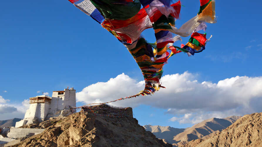 FILE - Prayer flags fly at Namgyal Tsemo Monastery above the town of Leh in Ladakh, India, Sept. 24, 2016.