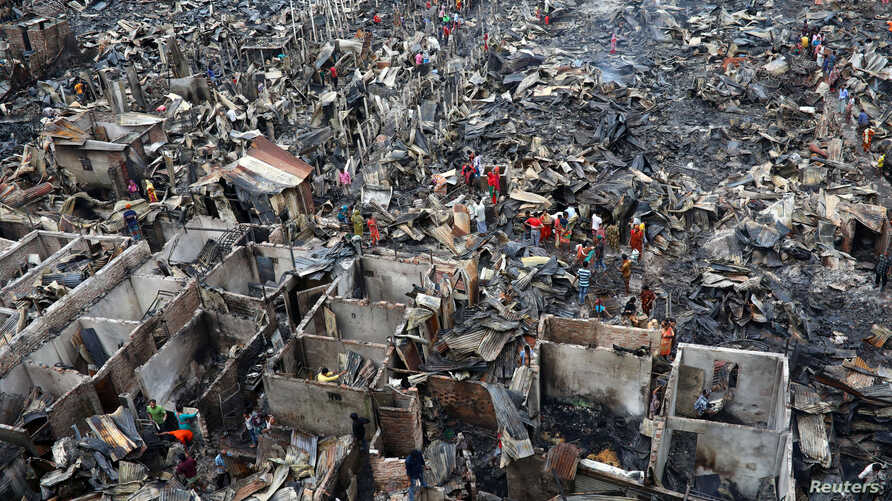 Slum dwellers search for their belongings from ashes after fire broke out on their shelters in Dhaka, Bangladesh, Aug. 17, 2019.