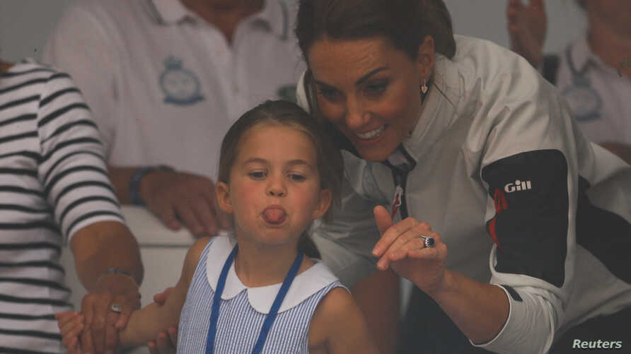 Britain's Princess Charlotte sticks her tongue out next to her mother, Catherine Duchess of Cambridge, before a presentation ceremony following the King's Cup Regatta in Isle of Wight.