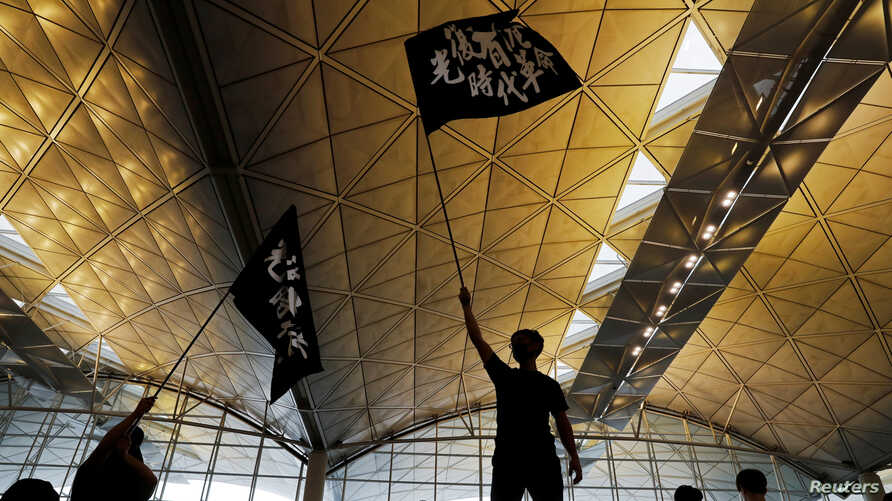 """Anti-extradition bill protesters wave flags with Chinese calligraphy that reads """"Liberate Hong Kong, the revolution of our times,"""" at a mass demonstration at Hong Kong International Airport, in Hong Kong, China, Aug. 12, 2019."""