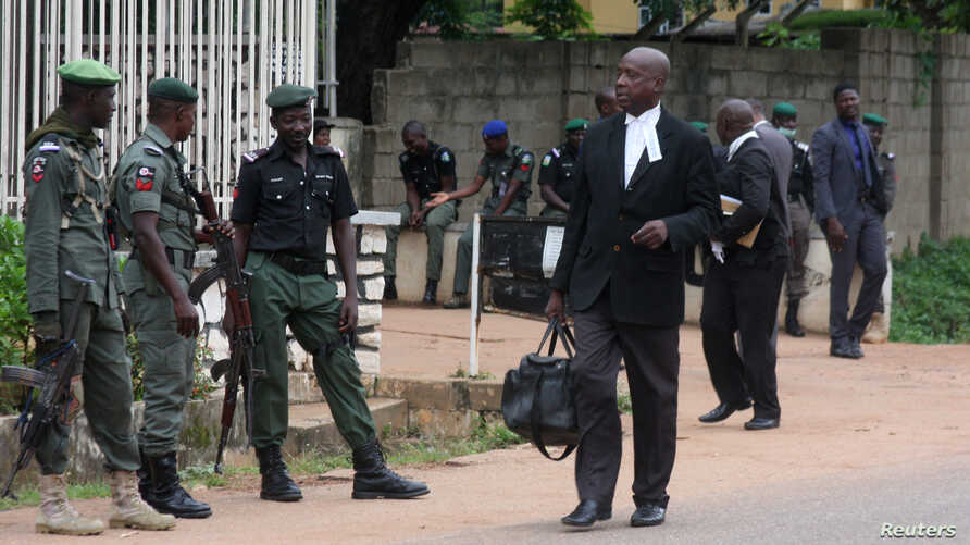 Lawyers walk past police officers standing guard outside a court, that is set to rule on Shi'ite leader Zakzaky's bail application, in Kaduna, Nigeria July 29, 2019.