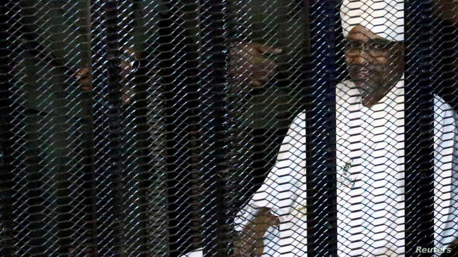 Sudan's former president Omar Hassan al-Bashir sits guarded inside a cage at the courthouse where he is facing corruption charges, in Khartoum, Aug. 19, 2019.