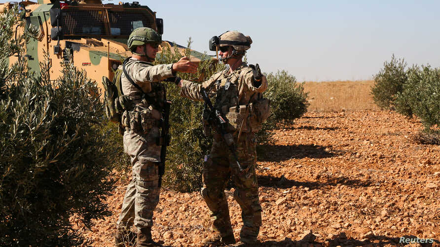 U.S. and Turkish soldiers discuss details during the first-ever combined joint patrol in Manbij, Syria, Nov. 1, 2018. (Courtesy: Arnada Jones/U.S. Army/Handout)