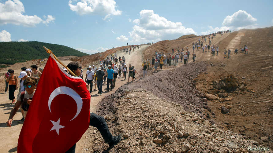 Environmental activists take part in a march to protest against what they say will be pollution from a foreign-owned gold mine project near the western town of Kirazli in Canakkale province, Turkey, Aug. 5, 2019.
