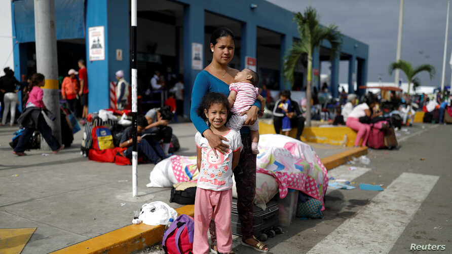 FILE - Venezuelan migrant Nemesis Ramirez, 22, poses for a picture with her children, while they wait to process their documents at the Ecuadorian-Peruvian border service center, before they continue their journey, June 17, 2019.