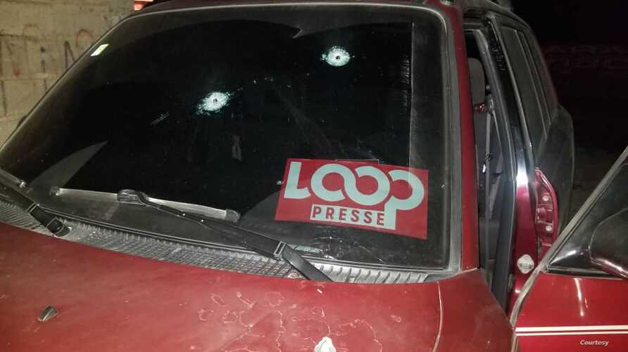 Luckson Saint Vil's car is seen with bullet holes piercing the windshield and hood.