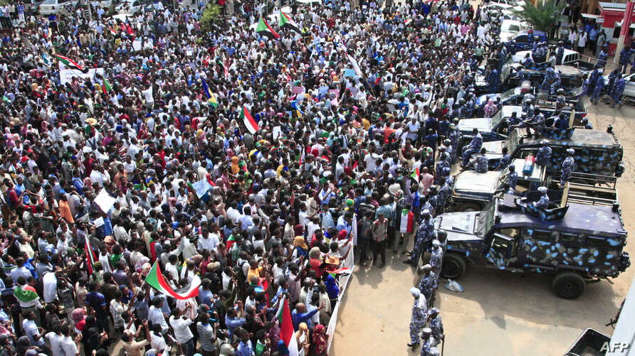 People rally before security forces' vehicles at a mass demonstration near the presidential palace in Sudan's capital, Khartoum, Sept. 12, 2019.