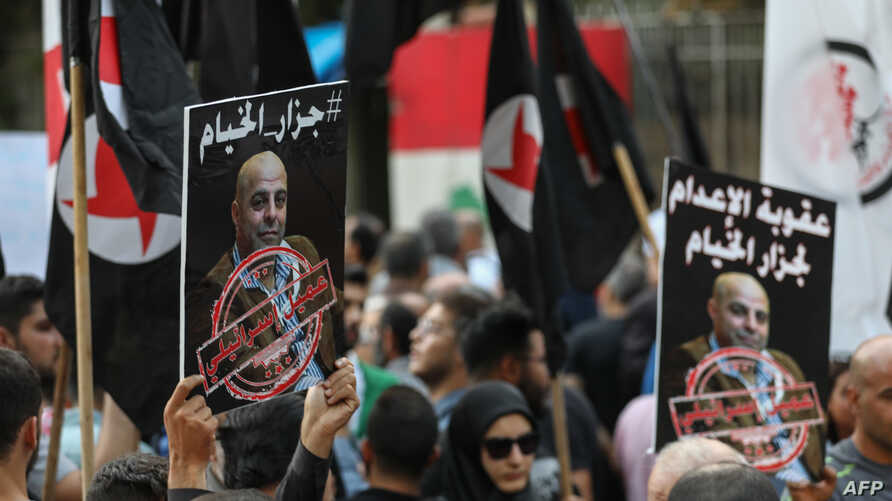 Former detainees of the pro-Israel South Lebanon Army (SLA) militia hold posters depicting former SLA member Amer Fakhoury during a demonstration denouncing his return, outside the Justice Palace in the Lebanese capital, Beirut, Sept. 12, 2019.