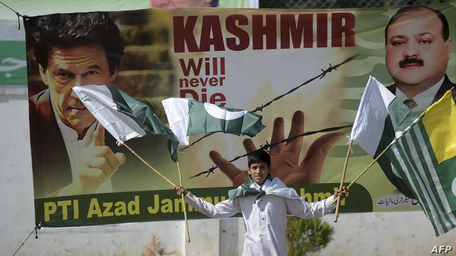 A Pakistani Kashmiri youth holds Pakistani and Kashmiri flags as he walks past a banner featuring a photograph of Pakistan's Prime Minister Imran Khan, left, during a rally in Muzaffarabad, Sept. 13, 2019.