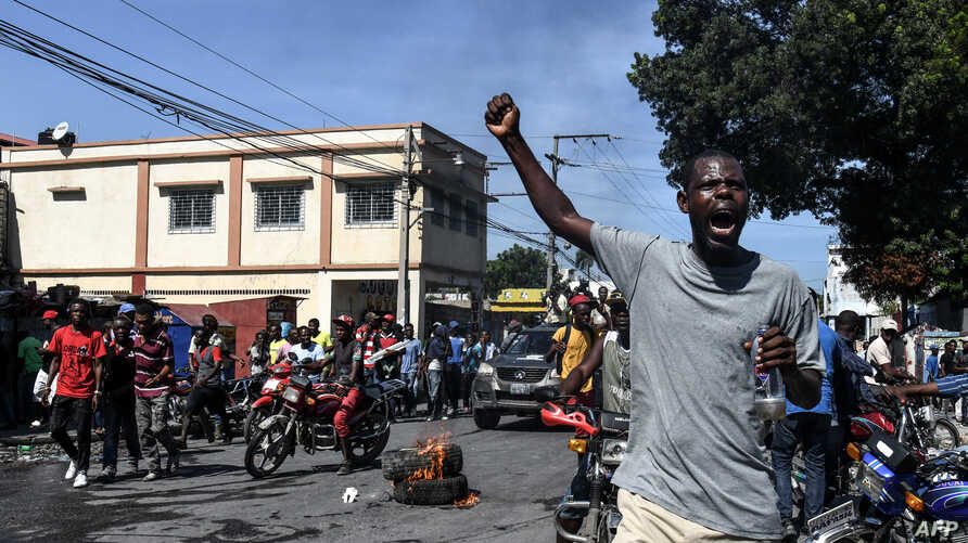 Demonstrators march on the street near parliament as they protest against ruling government in Port-au-Prince, Sept. 23, 2019.