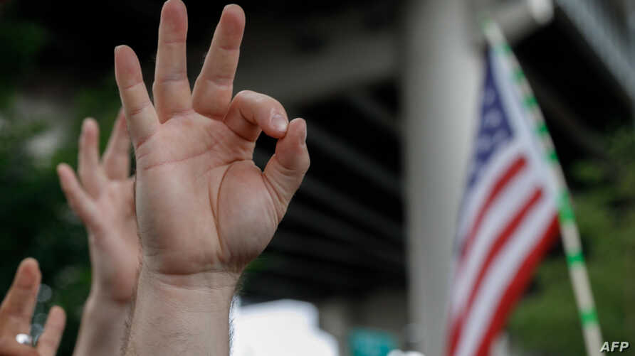 FILE - A demonstrator makes a hand gesture believed to have white supremacist connotations, Aug. 17, 2019, in Portland, Ore. The
