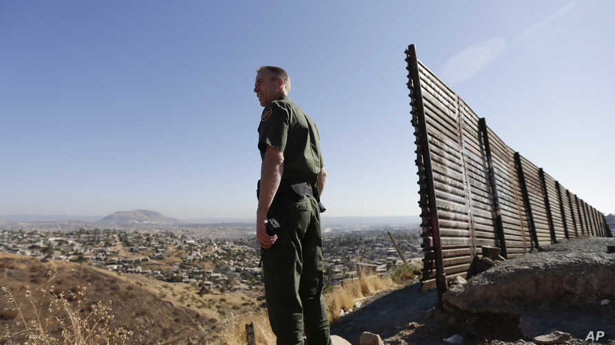 FILE - In this June 13, 2013 file photo, US Border Patrol agent Jerry Conlin looks out over Tijuana, Mexico