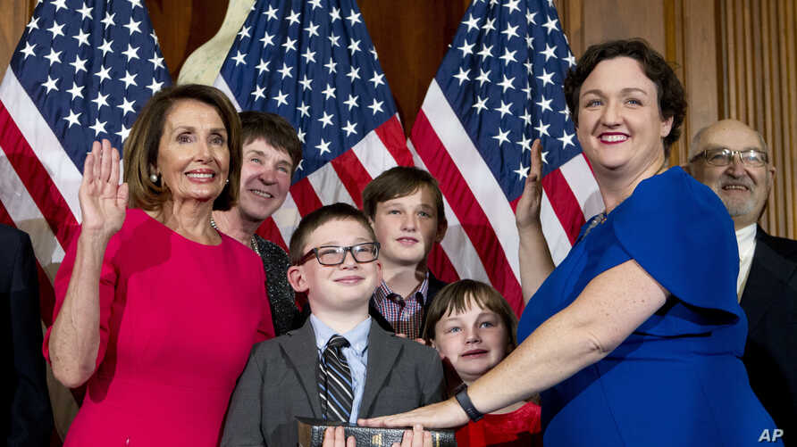 House Speaker Nancy Pelosi of Calif., administers the House oath of office to Rep. Katie Porter, D-Calif.,