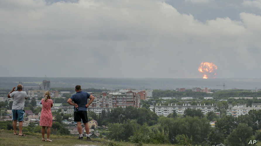FILE - People watch explosions at a military ammunition depot near the city of Achinsk in eastern Siberia, Aug. 5, 2019. On Monday, a gas canister exploded at the Russian State Center for Research on Virology and Biotechnology in Siberia.