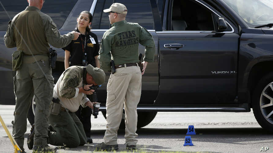 Law enforcement officials process a scene involved in Saturday's shooting, Sunday, Sept. 1, 2019, in Odessa, Texas.
