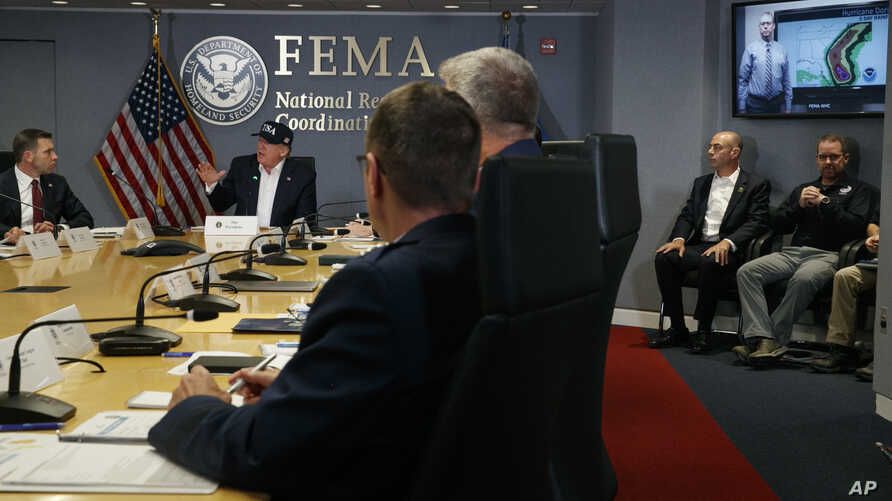 President Trump, left, listens as Kenneth Graham, director of NOAA's National Hurricane Center, on screen, gives an update during a briefing about Hurricane Dorian at the Federal Emergency Management Agency (FEMA), Sunday, Sept. 1, 2019.