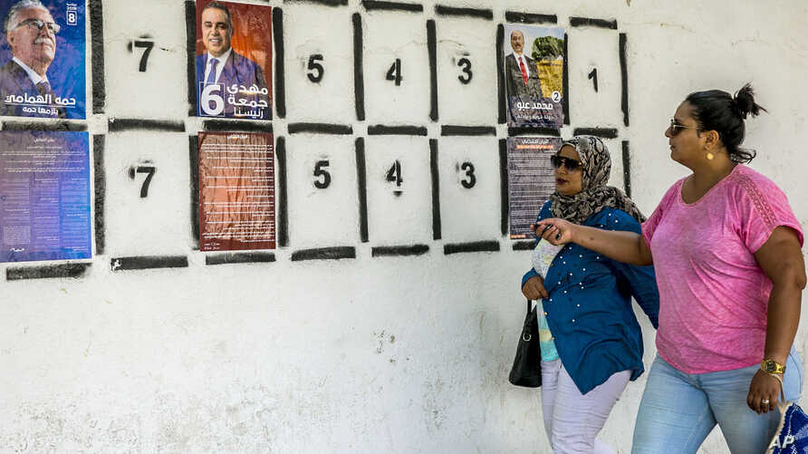 Women walk past a wall of campaign posters in Tunis, Tunisia, Sept. 2, 2019.