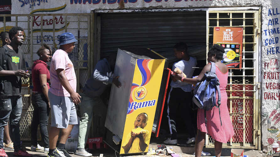 Looters make off with goods from a store on the outskirts of Johannesburg, Sept. 2, 2019.