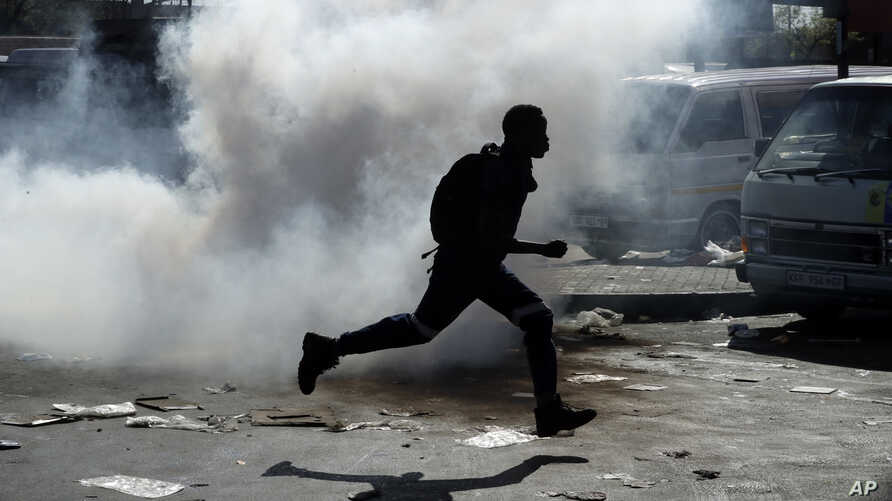 A man runs away from tear gas after making off with goods from a store in Germiston, east of Johannesburg, South Africa, Sept. 3, 2019.