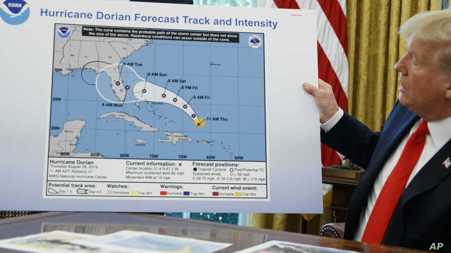 FILE - President Donald Trump holds a chart as he talks with reporters after receiving a briefing on Hurricane Dorian in the Oval Office of the White House, Sept. 4, 2019.
