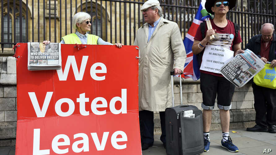 Pro Brexit demonstrators hold a placard outside the Houses of Parliament, in London, Sept. 5, 2019.