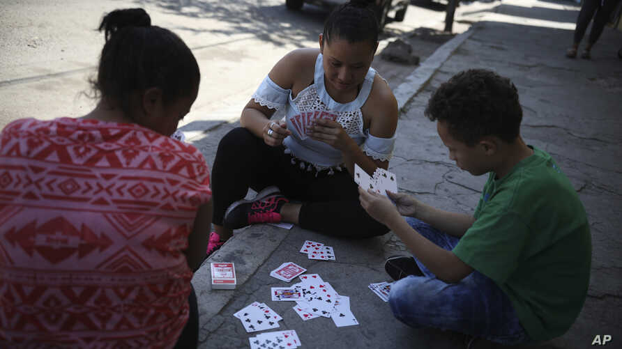 Dunea Romero of Honduras plays cards with her son and a friend from El Salvador outside the migrant shelter where they are staying while waiting to hear whether they will be granted U.S. asylum, in Tijuana, Mexico, Sept. 12, 2019.
