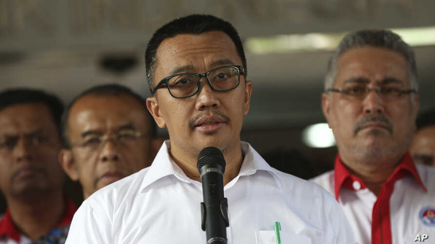 FILE - Indonesian Youth and Sports Minister Imam Nahrawi, center, speaks to the media during a press conference in Jakarta, Indonesia, Sept. 19, 2019.