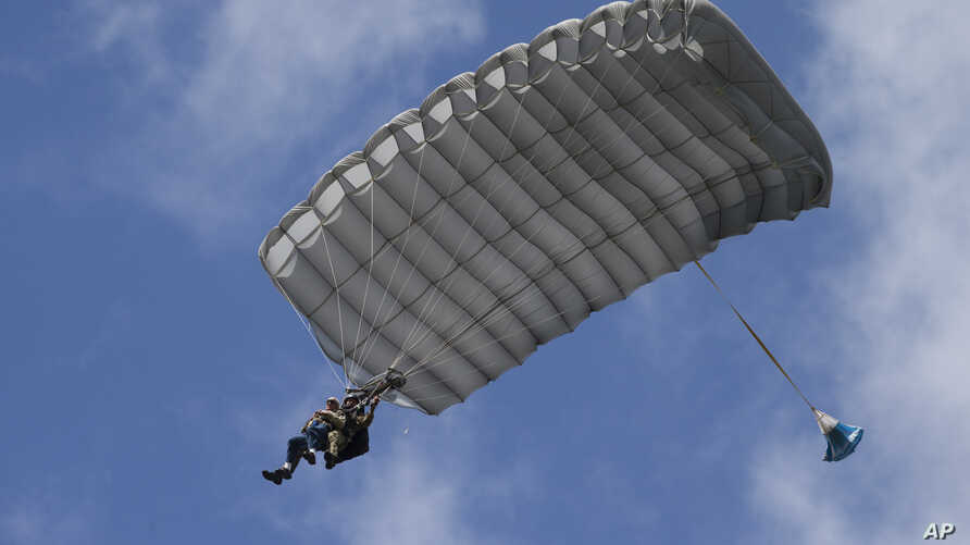 Tom Rice, a 98-year-old American WWII veteran, front left, approaches the landing zone during a tandem parachute jump near Groesbeek, Netherlands, Sept. 19, 2019.